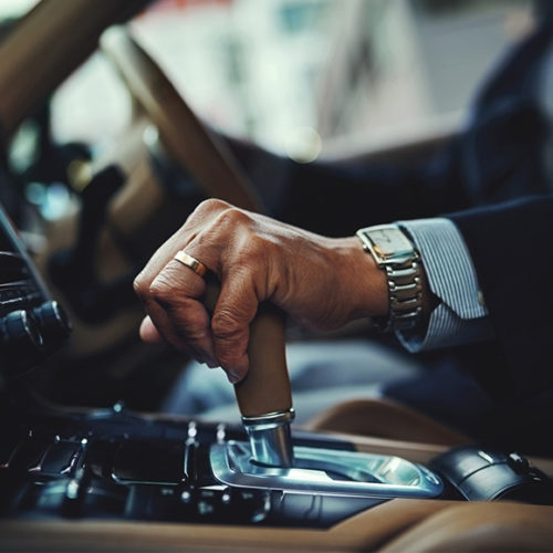 Photo of a man in a suit changing gear while driving - M&N Insurance